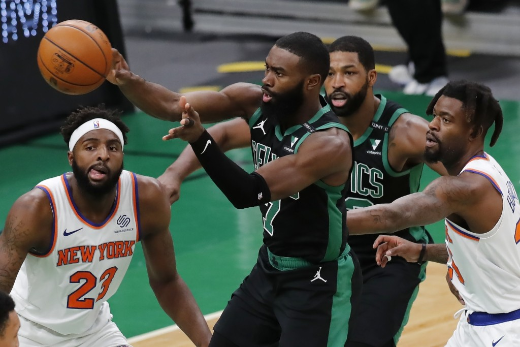 Boston Celtics' Jaylen Brown (7) passes off against New York Knicks' Mitchell Robinson (23) and Reggie Bullock, right, during the first half of an NBA...