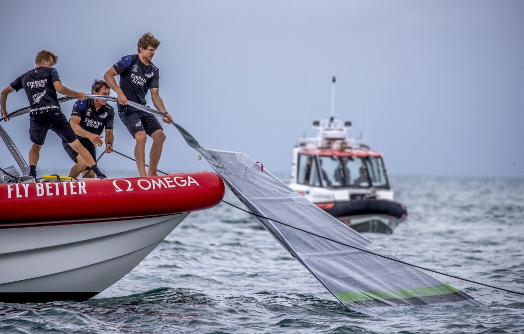 Team New Zealand crewmen grab the sail of United States' American Magic's boat, Patriot, after it capsized during its race against Italy's Luna Rossa ...