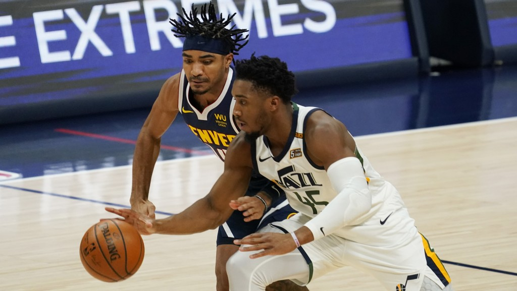 Utah Jazz guard Donovan Mitchell, front, pursues the ball with Denver Nuggets guard Gary Harris in the first half of an NBA basketball game Sunday, Ja...
