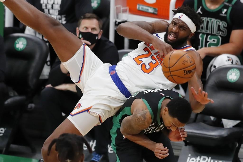 New York Knicks' Mitchell Robinson (23) falls on Boston Celtics' Jeff Teague during the first half of an NBA basketball game, Sunday, Jan. 17, 2021, i...
