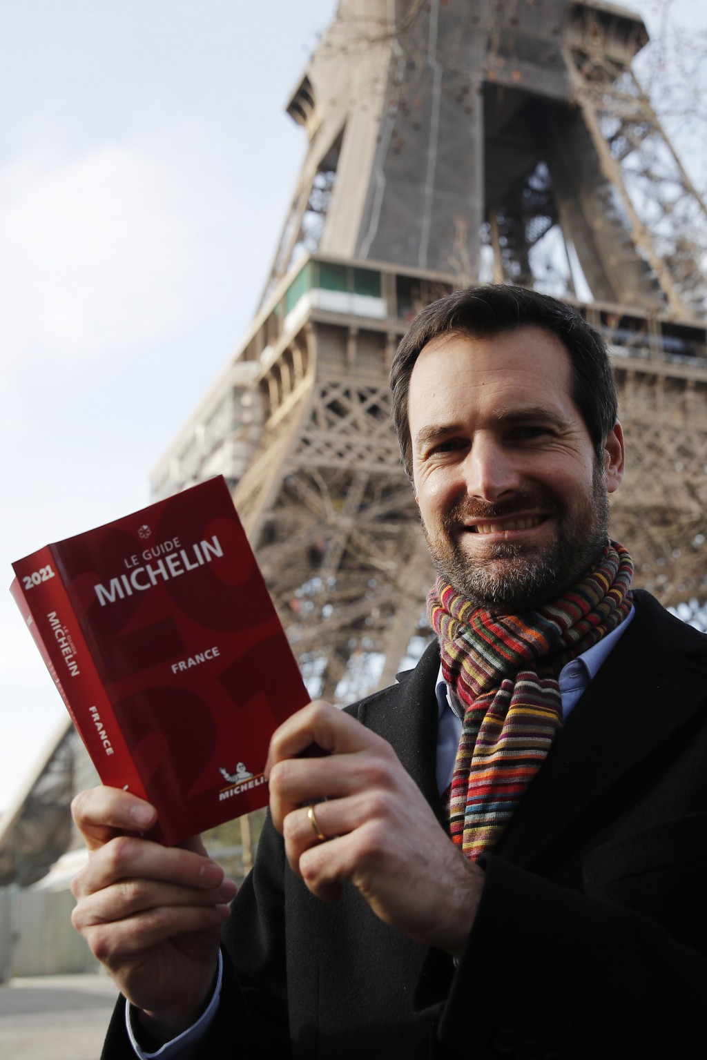 Gwendal Poullennec, head of Le Guide Michelin, poses with the 2021 edition outside the Eiffel Tower, Monday, Jan. 18, 2021 in Paris. Michelin will lat...
