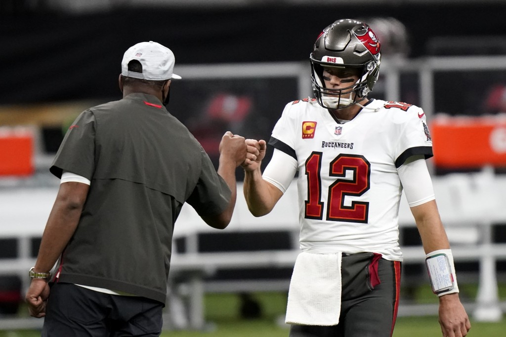 Tampa Bay Buccaneers quarterback Tom Brady (12) fist bumps with a coach before the first half of an NFL divisional round playoff football game between...