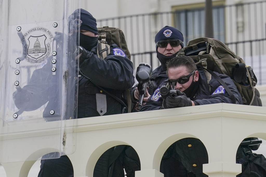 FILE - In this Jan. 6, 2021, file photo police keep a watch on rioters who tried to break through a police barrier at the Capitol in Washington. (AP P...