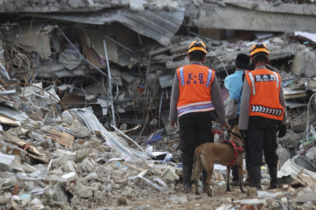 Rescuers leading a sniffer dog pause during a search operation at the ruins of a building collapsed in Friday's earthquake in Mamuju, West Sulawesi, I...