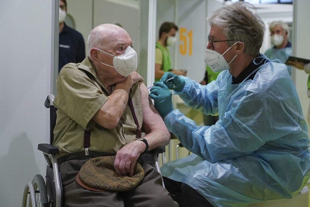 A doctor inoculates Herri Rehfeld, 92, against the new coronavirus with the Pfizer/BioNTech vaccine at the vaccination center at the Messe Berlin trad...