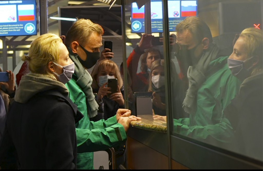 In this grab taken from video, Alexei Navalny and his wife Yulia stand at the passport control before Navalny was detained by police after arriving at...