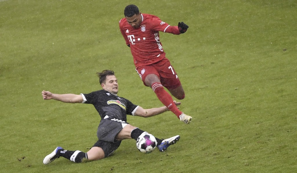 Freiburg's Amir Abrashi, left, is in action against Bayern's Serge Gnabry, right, during the Bundesliga soccer match between Bayern Munich and SC Frei...