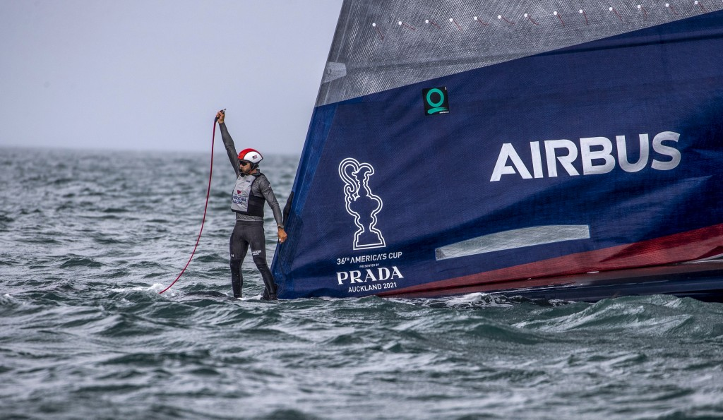 A crewman from United States' American Magic boat Patriot signals for assistant after it capsized during its race against Italy's Luna Rossa on the th...