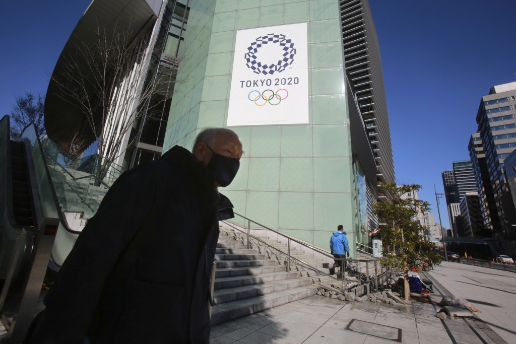 A man walks by the logo of Tokyo Olympic Games planned to start in the summer of 2021, in Tokyo, Tuesday, Jan. 19, 2021. Tokyo organizers have no publ...