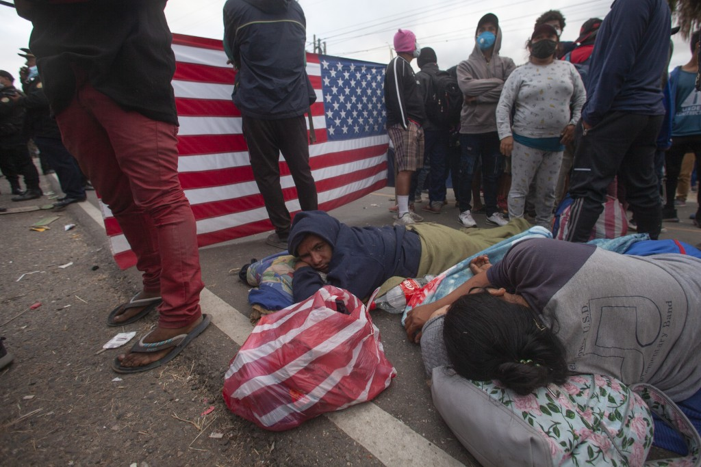 Honduran migrants rest as they are blocked by Guatemalan soldiers and police from advancing toward the US border, on the highway in Vado Hondo, Guatem...