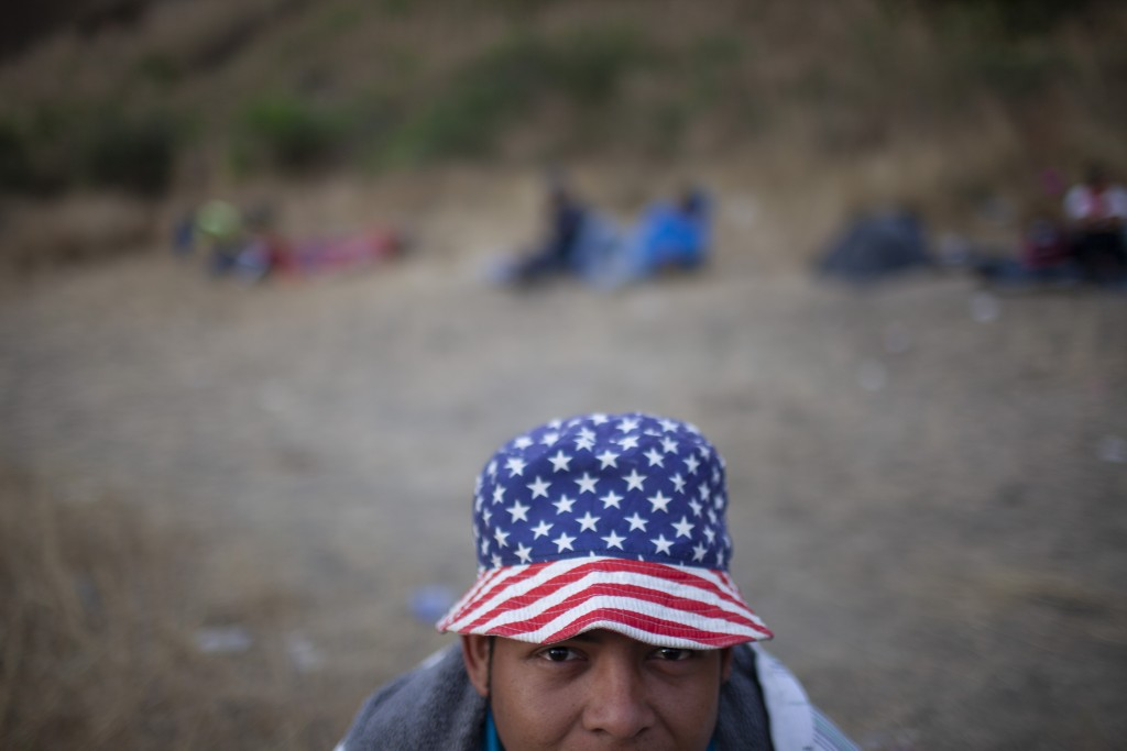 A Honduran migrant wearing a hat with the stars and stripes, poses for a photo at a road block manned by Guatemalan soldiers and police, on the highwa...