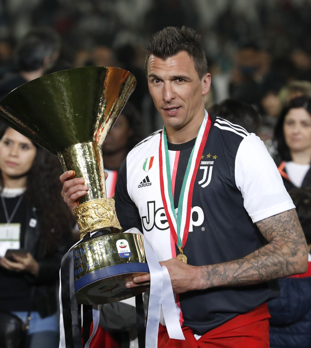 FILE - In this May 19, 2019 file photo, Juventus' Mario Mandzukic holds the Serie A soccer title trophy, at the Allianz Stadium in Turin, Italy. AC Mi...