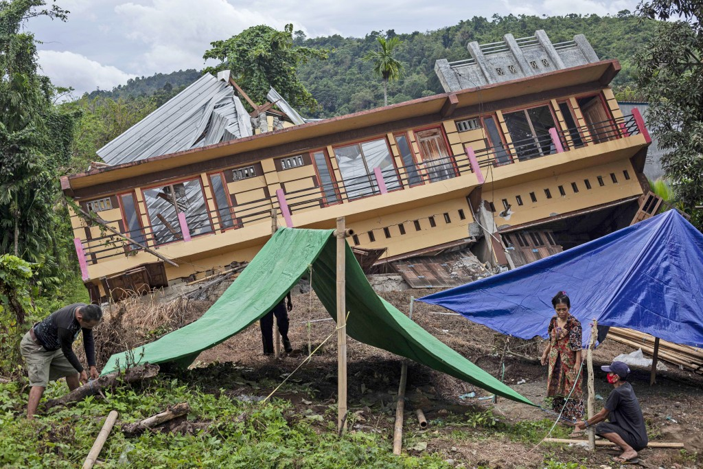 Residents build tents outside their house badly damaged by earthquake in Mamuju, West Sulawesi, Indonesia, Tuesday, Jan. 19, 2021. Aid was reaching th...