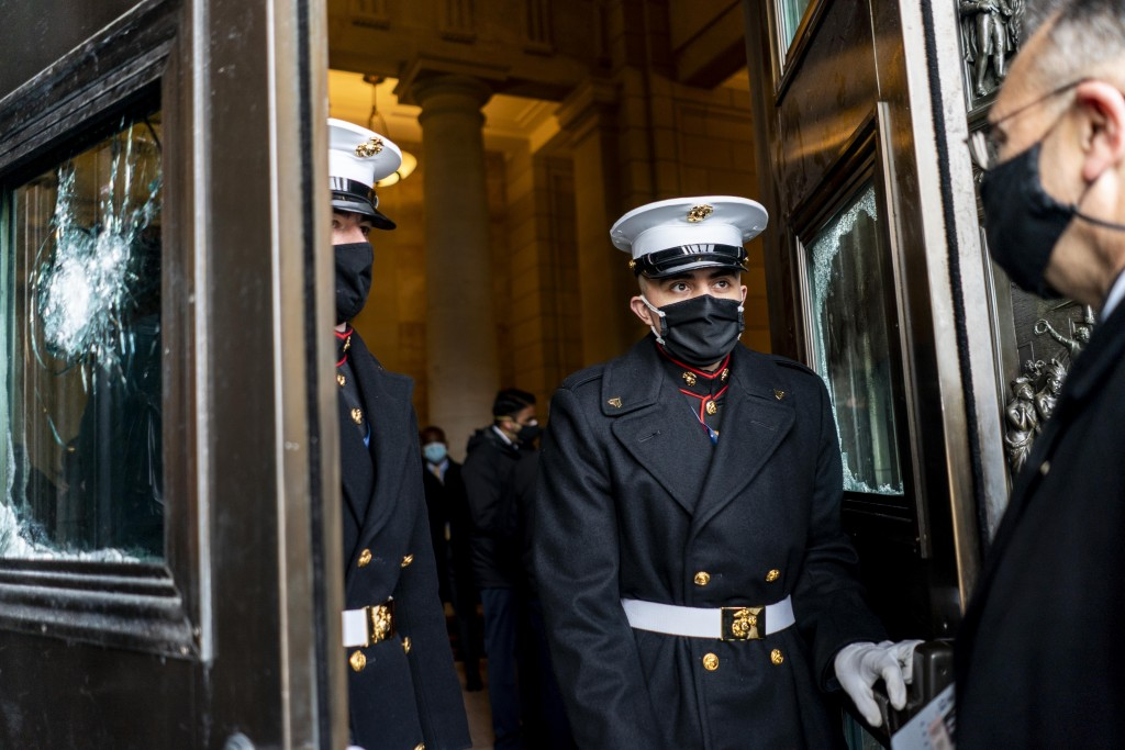 U.S. Marine Corps. stand in the doorway between damaged Capitol doors during a rehearsal for the 59th inaugural ceremony for President-elect Joe Biden...
