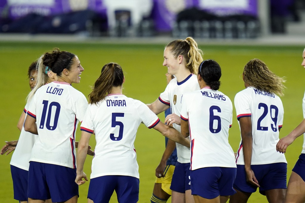 United States midfielder Samantha Mewis, center, celebrates after scoring a goal against Colombia on a penalty kick with teammates forward Carli Lloyd...