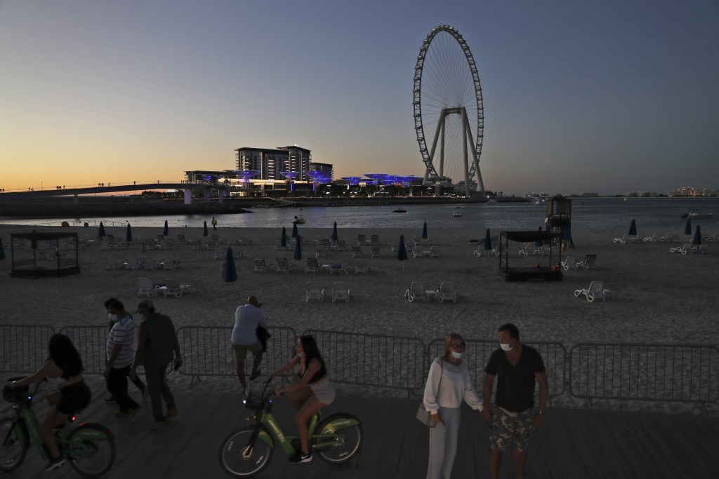 Tourists and residents enjoy the sunset at the Jumeirah Beach Residence, in Dubai, United Arab Emirates, Tuesday, Jan. 12, 2021. Coronavirus infection...