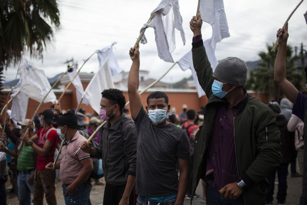 Honduran migrants raise white flags as they are blocked by Guatemalan soldiers and police from advancing toward the US border, on the highway in Vado ...