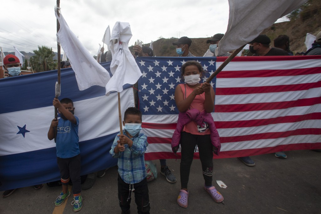 Honduran migrants raise white flags in front of a Honduran and American flag, as they are blocked by Guatemalan soldiers and police from advancing tow...