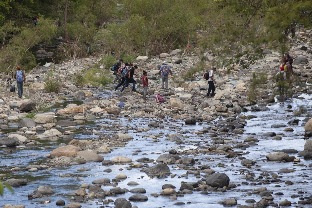 Honduran migrants walk away from clashes with Guatemalan soldiers and police blocking them from advancing toward the US, on the highway in Vado Hondo,...