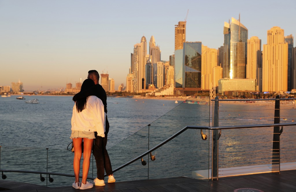 Tourists look at the skyline at sunset, in Dubai, United Arab Emirates, Tuesday, Jan. 12, 2021. Since becoming one of the world's first destinations t...