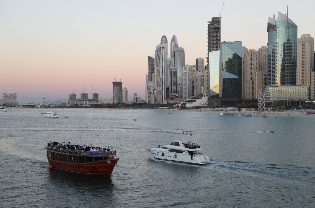 Tourists on a yacht as they pass a traditional dhow serving a dinner cruise, in Dubai, United Arab Emirates, Tuesday, Jan. 12, 2021. With peak tourism...
