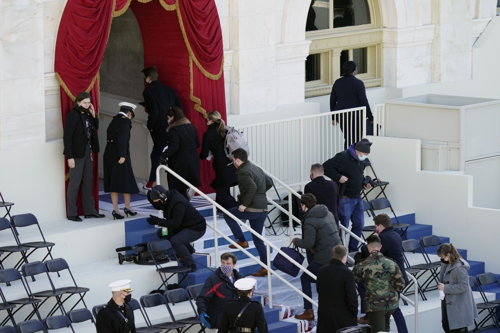 People evacuate from the West Front of the U.S. Capitol during a rehearsal the 59th Presidential Inauguration at the U.S. Capitol in Washington, Monda...