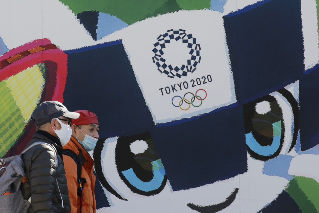 People walk by posters to promote the Tokyo 2020 Olympics planned to start in the summer of 2021, in Tokyo, Tuesday, Jan. 19, 2021. Tokyo organizers h...