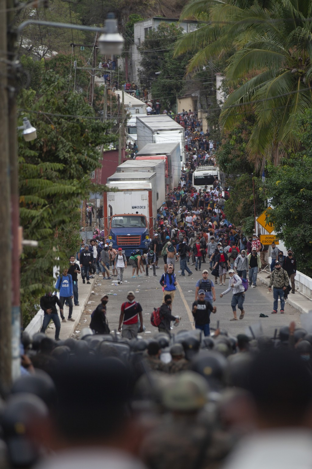 Honduran migrants, top, stand between cargo trucks as they confront Guatemalan soldiers and police blocking them from advancing toward the US, on the ...