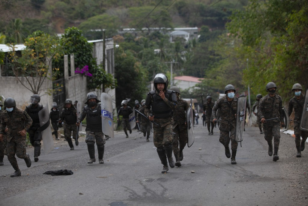 Guatemalan soldiers and police chase Honduran migrants as they try advancing toward the US border, on the highway in Vado Hondo, Guatemala, Monday, Ja...