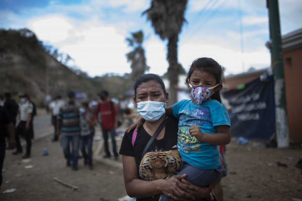 A woman and a girl walk away as Honduran migrants confront Guatemalan soldiers and police blocking them from advancing toward the US, on the highway i...