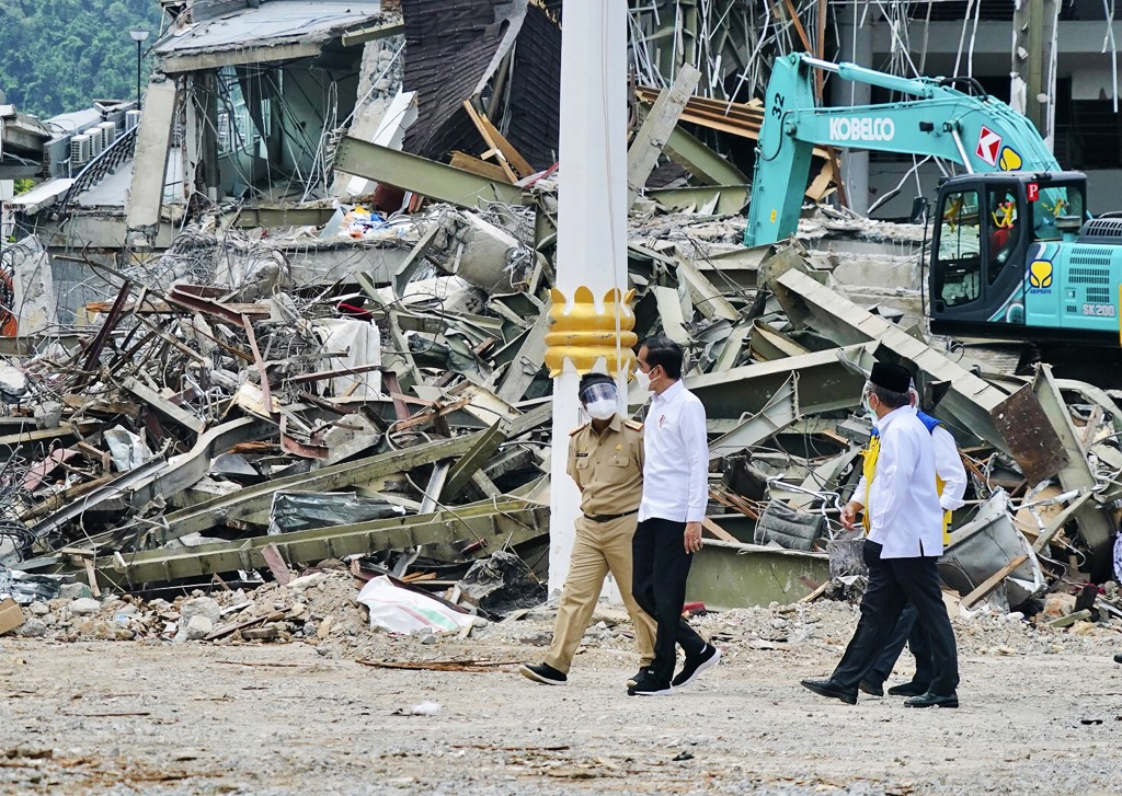 In this photo released by the Indonesian Presidential Palace, President Joko Widodo, center, talks to an official as he inspects an earthquake-damaged...