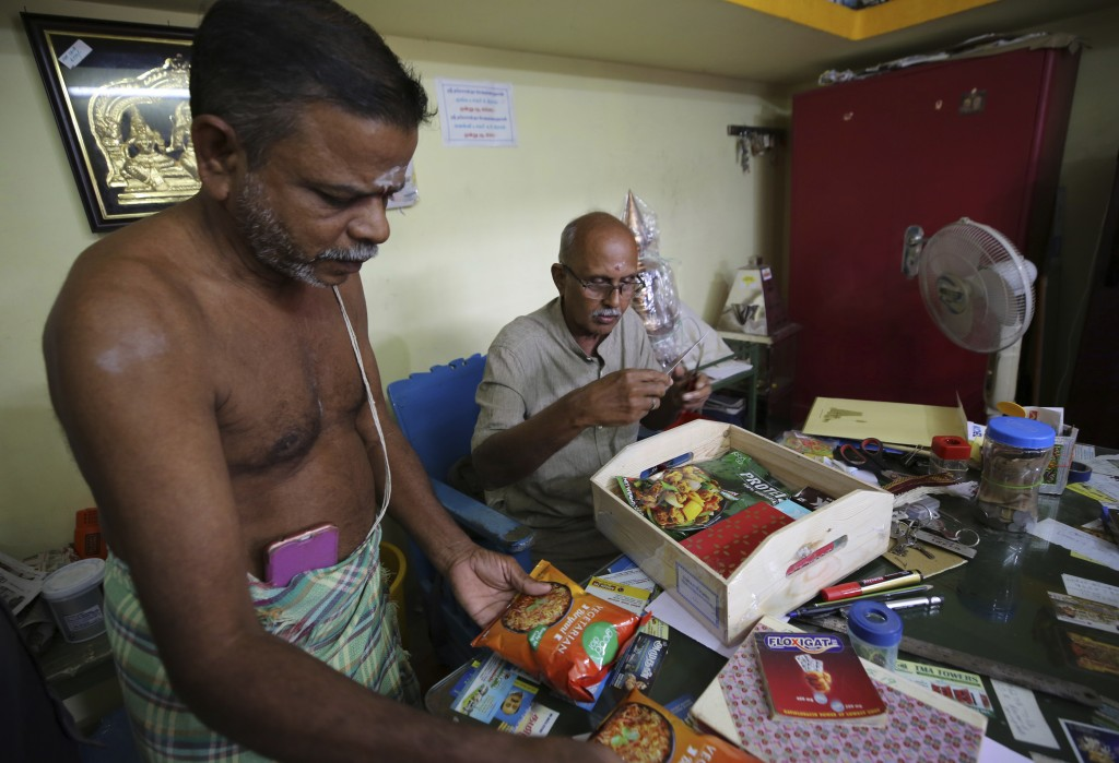 A Hindu priest, left, and a temple official open a box full of packaged food and sweets sent by a non-government organization to be distributed among ...