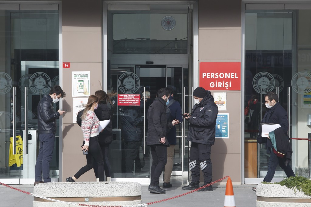 A security official checks people's IDs before the third hearing in the trial of Carlos Ghosn, former Nissan Motor Co. chairman, in Istanbul, Wednesda...
