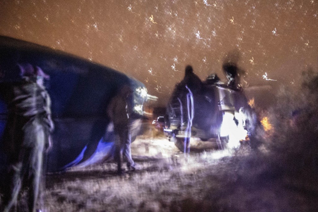 Smugglers gather near and pause atop a vehicle as they attempt to lift a fishing boat in a remote desert out of the town of Dakhla in Morocco-administ...