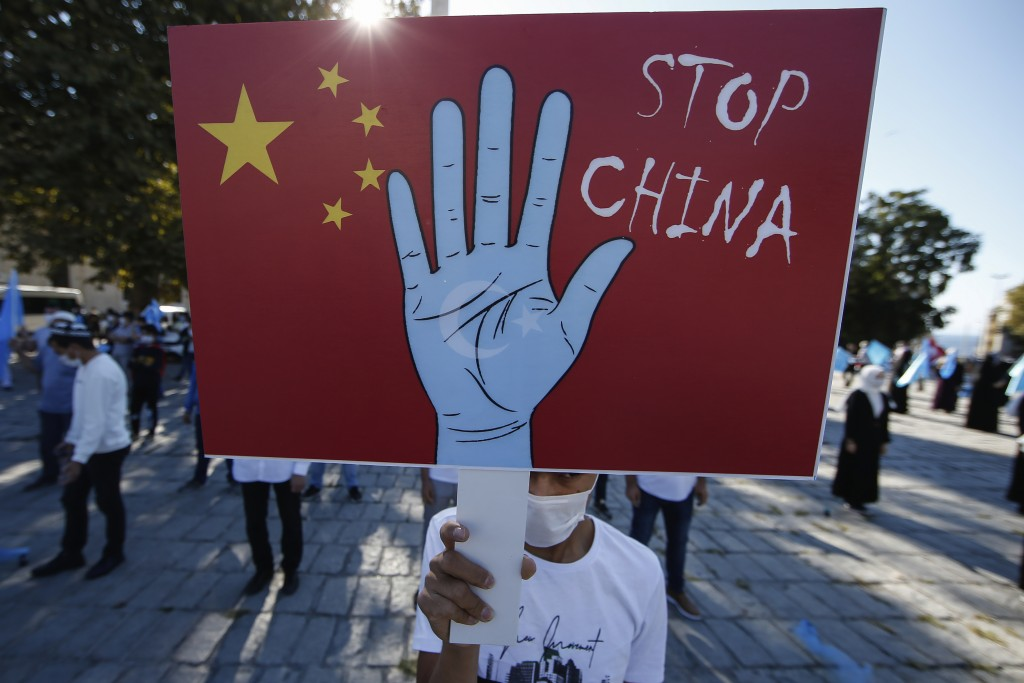 圖為2020年10月1日維吾爾族民眾在土耳其手持標語,抗議中共在新疆的種族滅絕暴行(美聯社圖片)