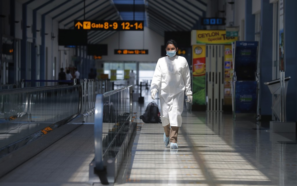 A Sri Lankan airport worker in protective suit walks inside a terminal at the Katunayake International Airport in Colombo, Sri Lanka, Wednesday, Jan. ...