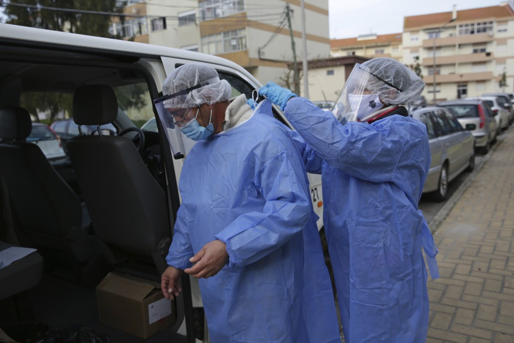 Municipal workers remove their protective gear after collecting presidential election ballots from an elderly care home in Montijo, south of Lisbon, T...