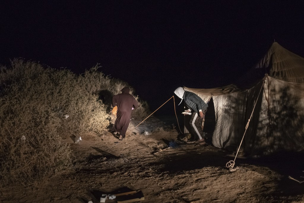 Smugglers walk past a tent that is used while building fishing boats intended to carry migrants to the Canary Islands, in a remote desert out of the t...