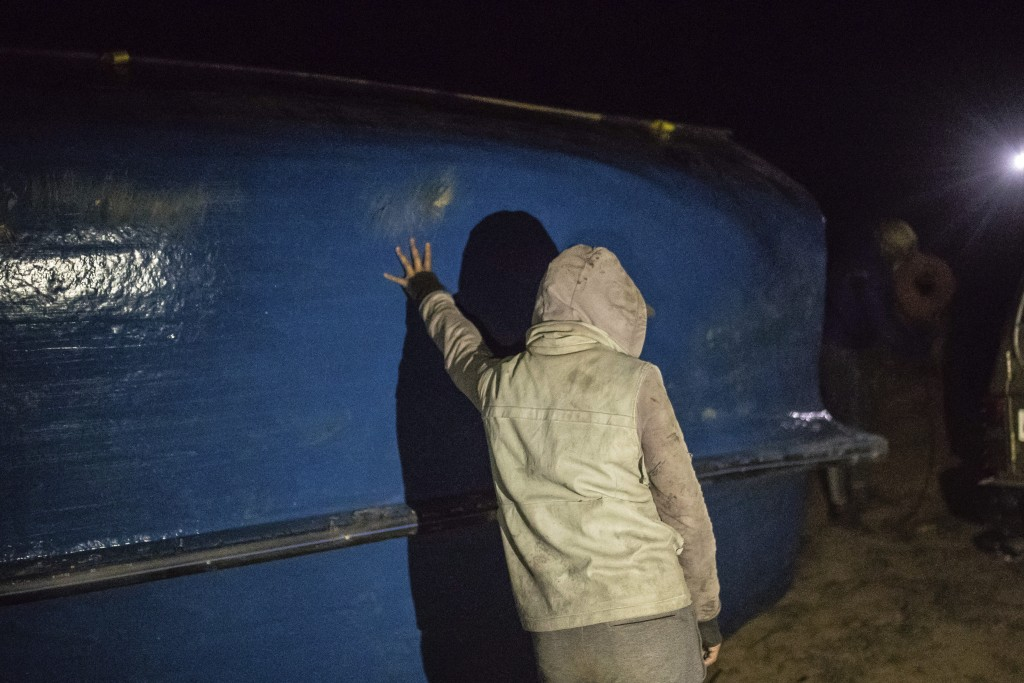 A smuggler pauses while lifting a fishing boat onto a vehicle in a remote desert out of the town of Dakhla in Morocco-administered Western Sahara, Tue...