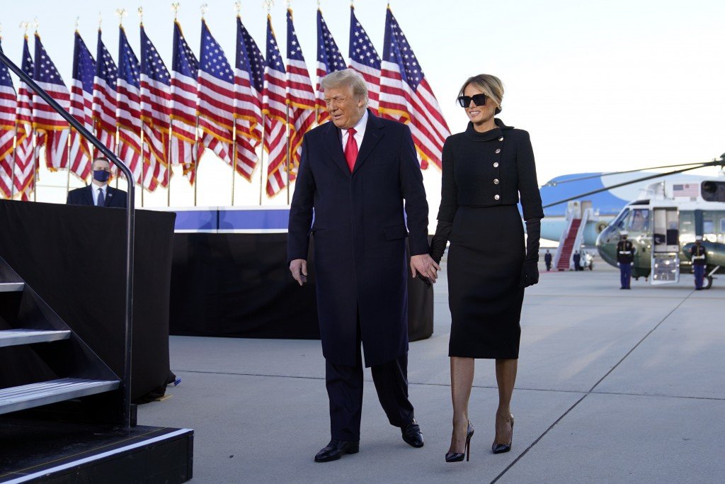President Donald Trump and first lady Melania Trump arrive to speak before they board Air Force One at Andrews Air Force Base, Md., Wednesday, Jan. 20...
