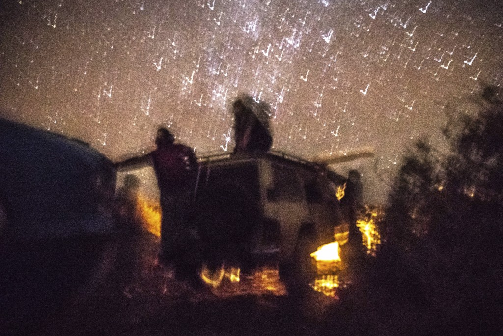 Smugglers pause atop a vehicle as they attempt to lift a fishing boat in a remote desert out of the town of Dakhla in Morocco-administered Western Sah...