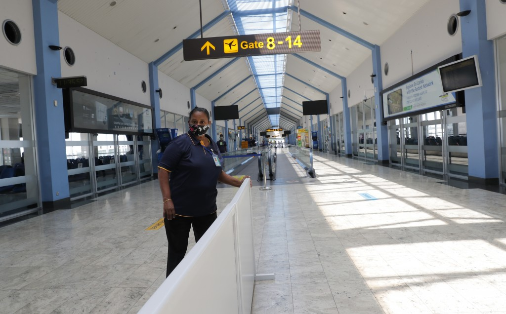 A Sri Lankan airport worker arranges a partition inside a terminal at the Katunayake International Airport in Colombo, Sri Lanka, Wednesday, Jan. 20, ...