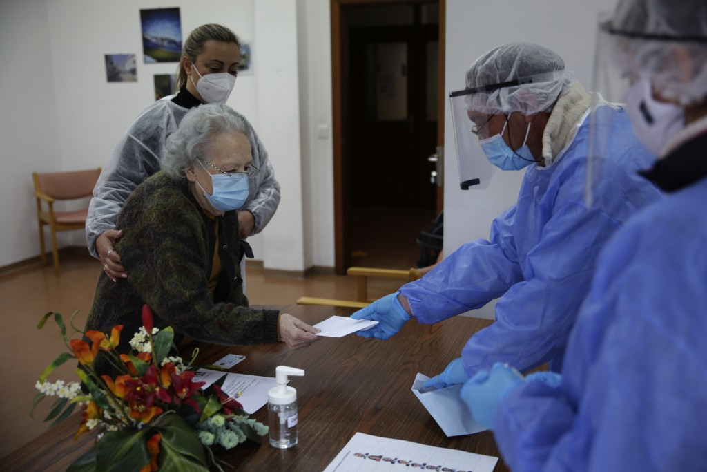 Rosa Gordo, 89, hands her presidential election ballot to municipal workers in protective gear at the elderly care home where she resides in Montijo, ...