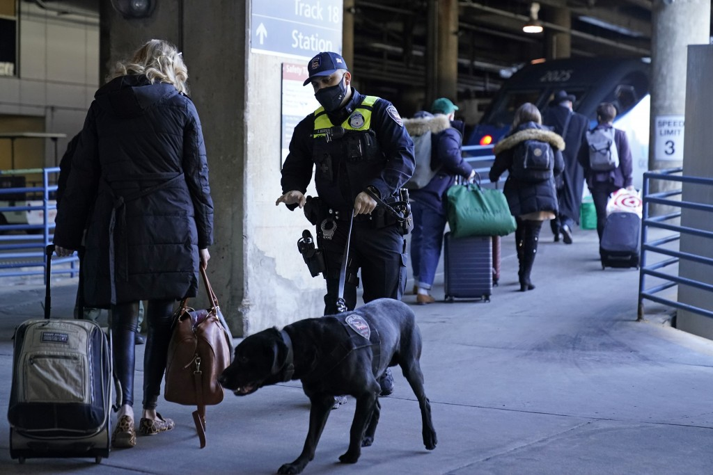 An Amtrak K9 officer and his dog check passengers before they board an Amtrak train before its departure from Union Station as security is heightened ...