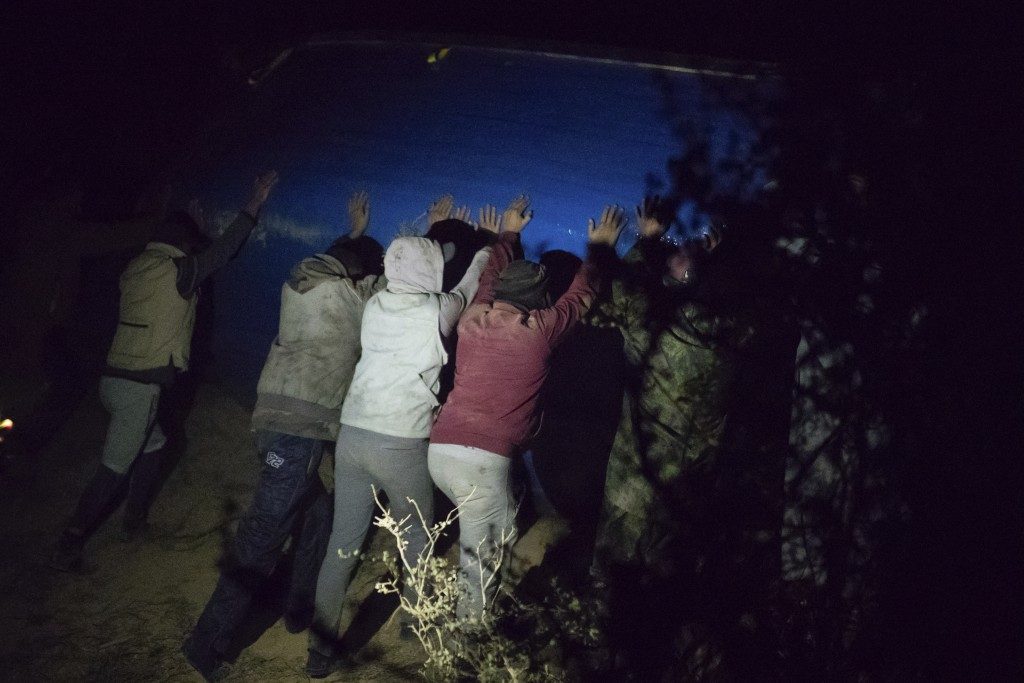 Smugglers turn over a fishing boat intended to carry migrants to the Canary Islands, in a remote desert out of the town of Dakhla in Morocco-administe...