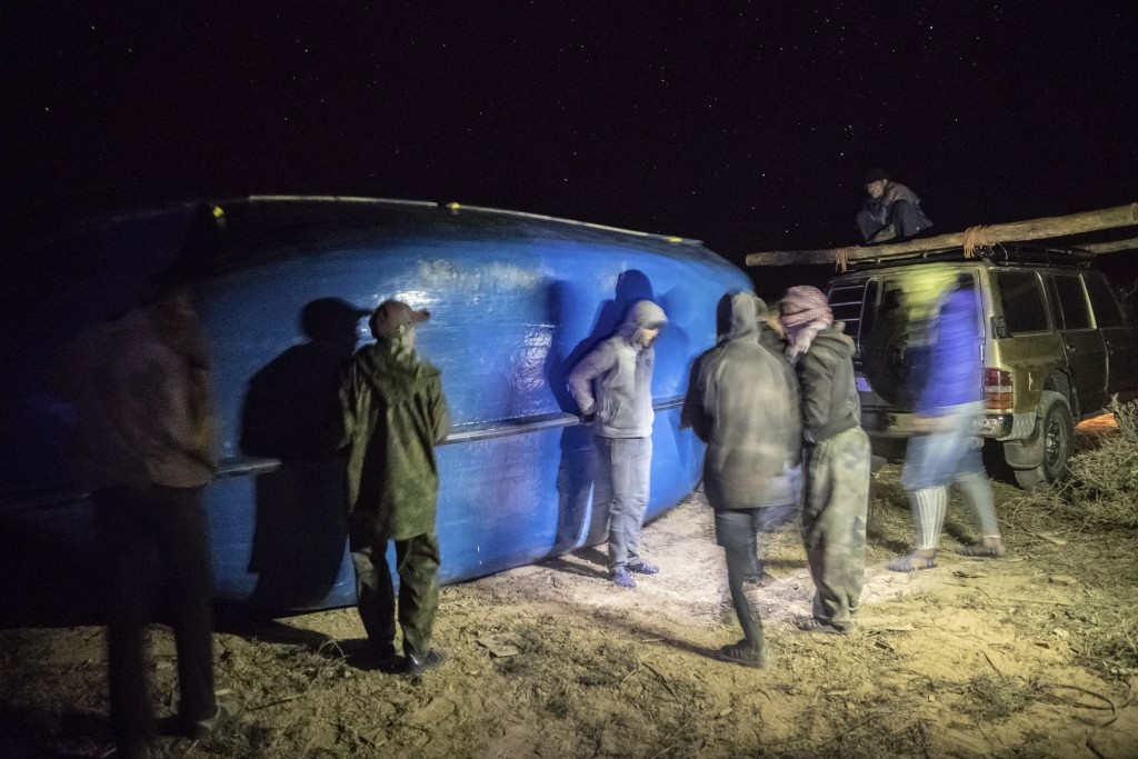 Smugglers lift onto a vehicle a fishing boat intended to carry migrants to the Canary Islands, in a remote desert out of the town of Dakhla in Morocco...