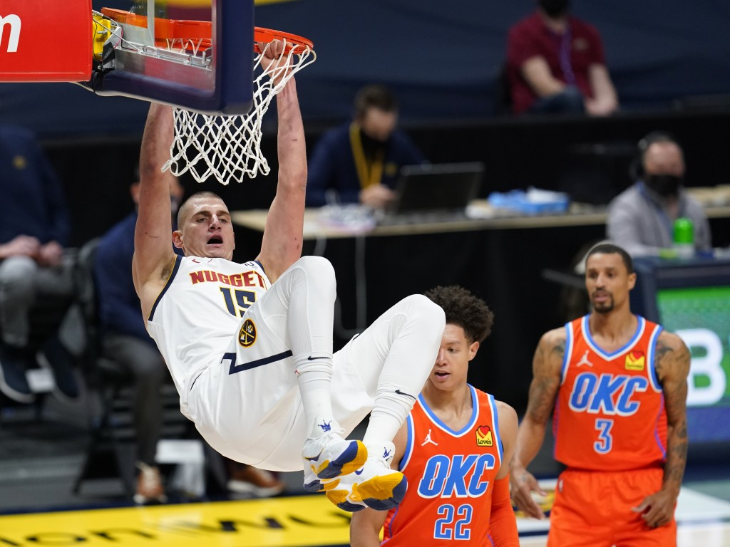 Denver Nuggets center Nikola Jokic, left, hangs from the rim after dunking the ball for a basket against Oklahoma City Thunder forward Isaiah Roby, ce...