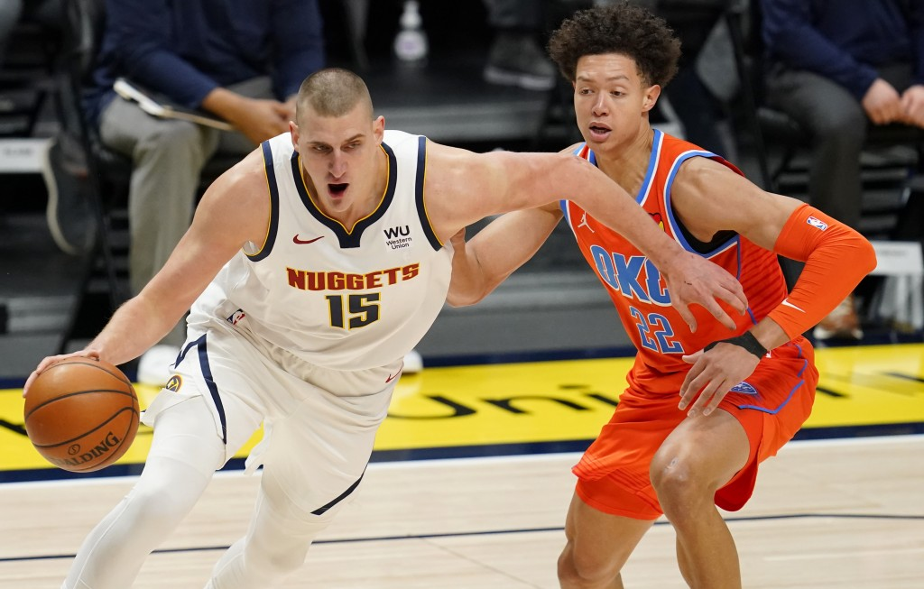 Denver Nuggets center Nikola Jokic, left, drives to the rim past Oklahoma City Thunder forward Isaiah Roby in the first half of an NBA basketball game...