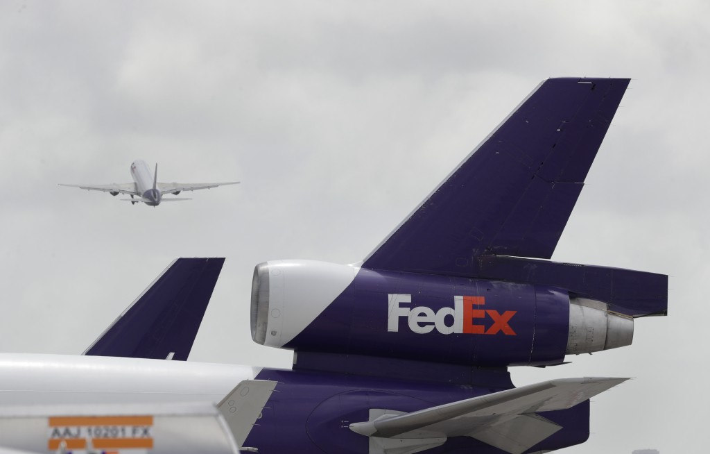 A FedEx aircraft takes off past the tail of another parked on the tarmac of Miami International Airport, Monday, July 27, 2020, in Miami. FedEx plans ...