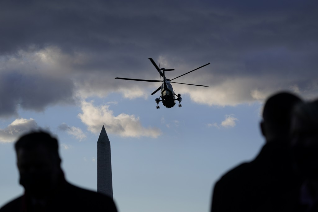 People watch as Marine One with President Donald Trump on board departs on the South Lawn of the White House, Wednesday, Jan. 20, 2021, in Washington....